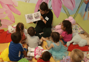Female volunteer reading to young children at Tu Nidito